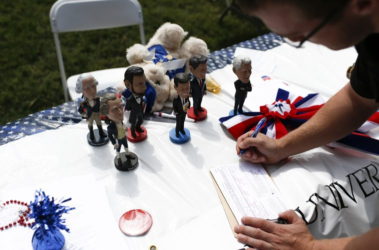 Political bobblehead figures sit as a WKU student fills out a voter registration card during the National Constitution Day outside of Grise Hall on September 16, 2016.