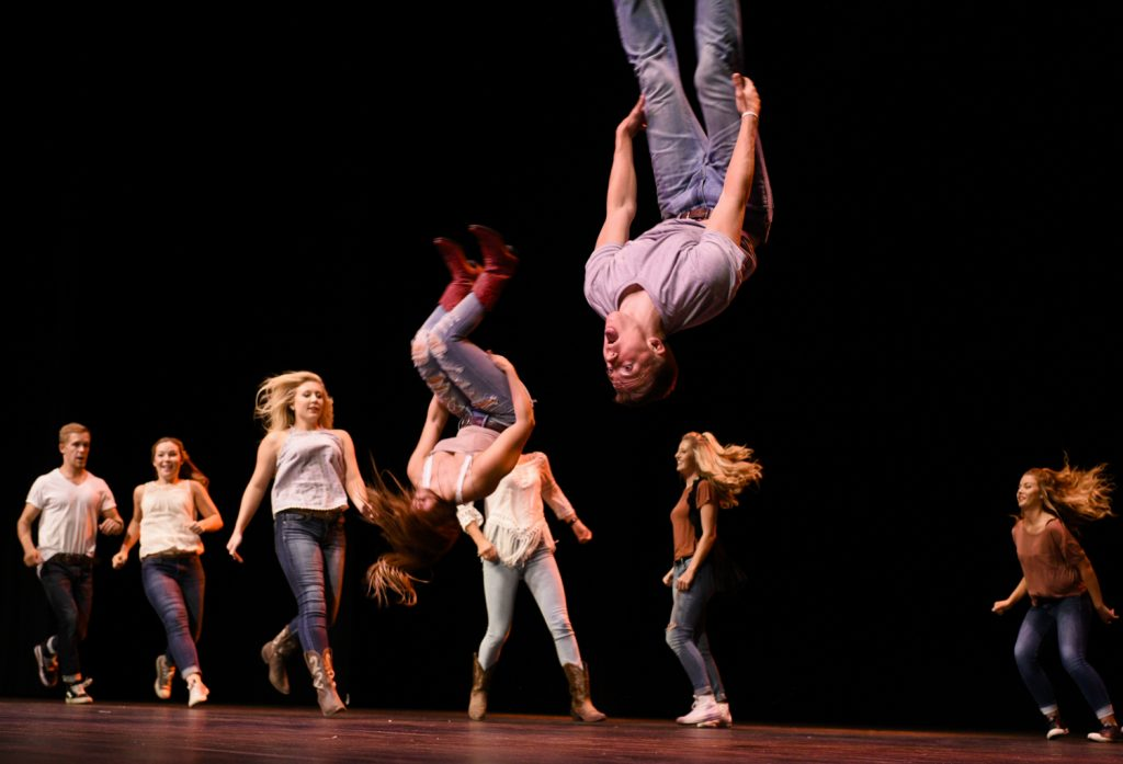 Members of Alpha Delta Pi sorority and Phi Gamma Delta fraternity do backflips for their Footloose-themed performance at SKyPAC on Oct. 4.