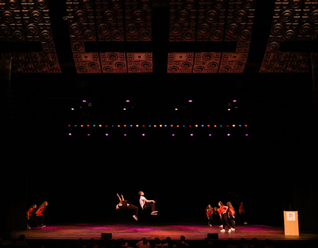 "Chi Omega sorority members and Sigma Nu fraternity members do backflips across the stage as they close out the show with their ""Banding Together to Find Our Sound"" performance at Shenanigans. Shenanigans was an annual fundraiser hosted by Kappa Delta sorority."