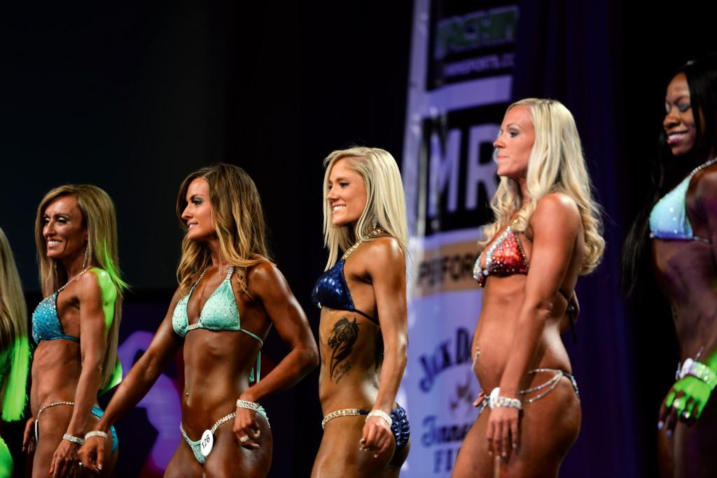 Crestwood junior Allie Boon, middle, waits to receive her sword after winning first place in the novice bikini competition. Boon also received a second-place award in the collegiate division.