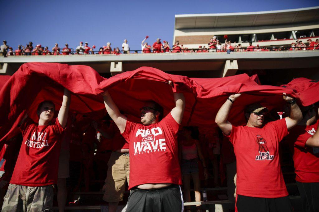 Stearns, Ky. junior, Adam Morgan, 19, Radcliff, Ky. freshman, Devin Wease, 19, and Bethpage, Tn. WKU alumni, William Cartledge, 27, hold up a Western Kentucky banner over the student section after a touchdown during the Vanderbilt game on Sept. 24, 2016 at L.T. Smith Stadium.