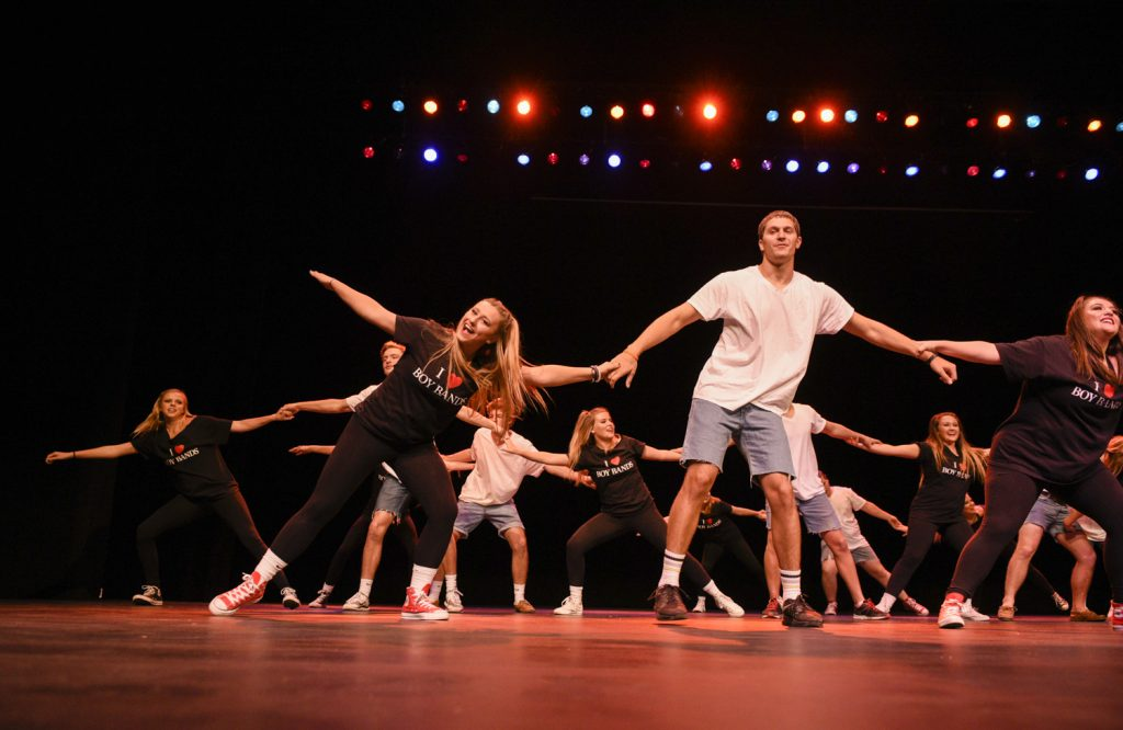 """Members of Alpha Xi Delta sorority, Kappa Alpha order and FarmHouse fraternity perform their """"Evolution of Boy Bands"""" routine on Oct. 4 at the SKyPAC theater. The Shenanigans event, a fundraiser for KD, packed the theater to its capacity."""
